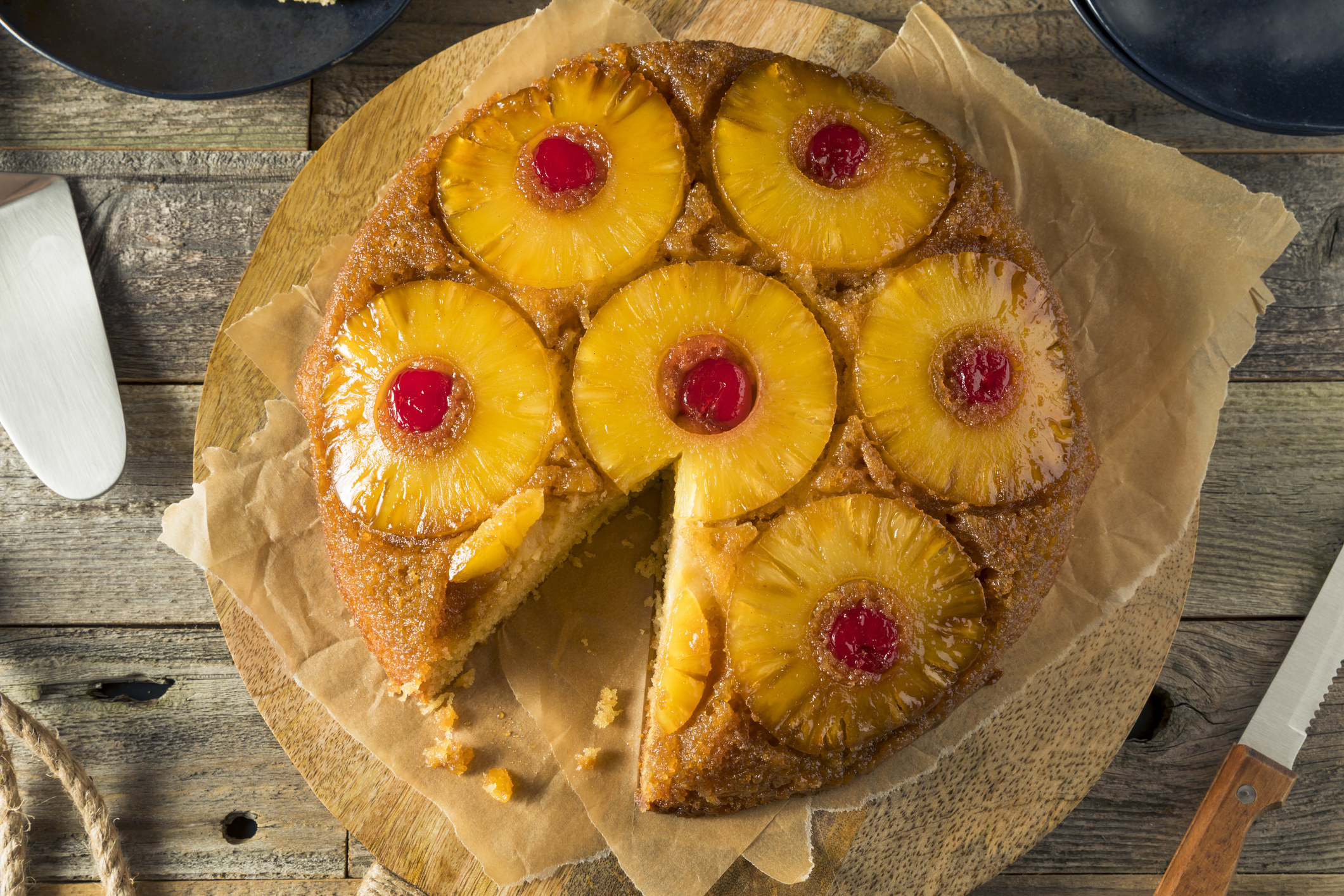 A cake with a slice taken out of it that has pineapple rings on top and cherries in the middle of the pineapple rings