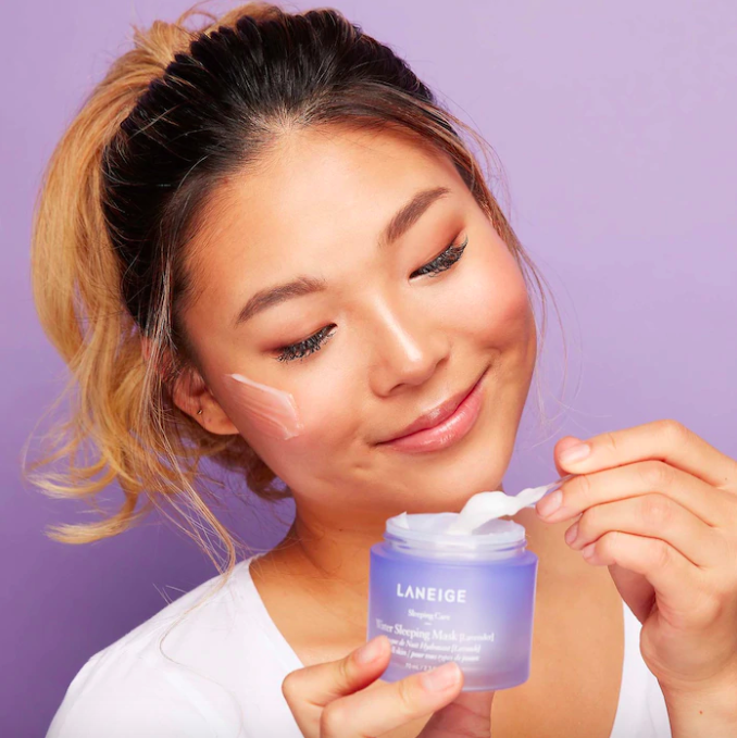 A smiling person applying the sleeping mask to their face