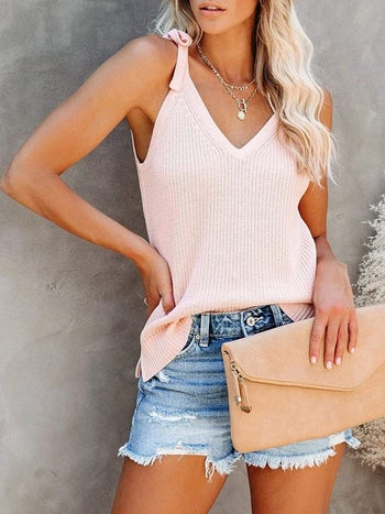 model wearing the top in pink with denim shorts