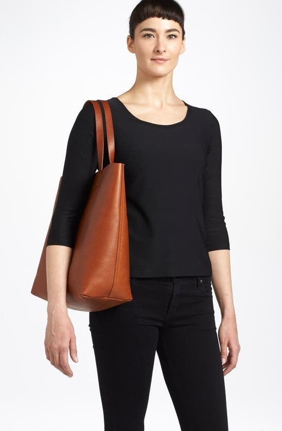 A model wears the tote in English Saddle