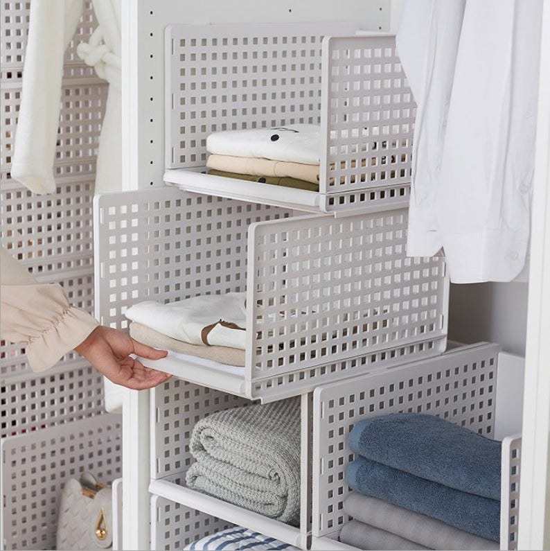 a hand reaching towards four white storage boxes stacked on top of each other, the boxes are holding towels, blankets, and clothing