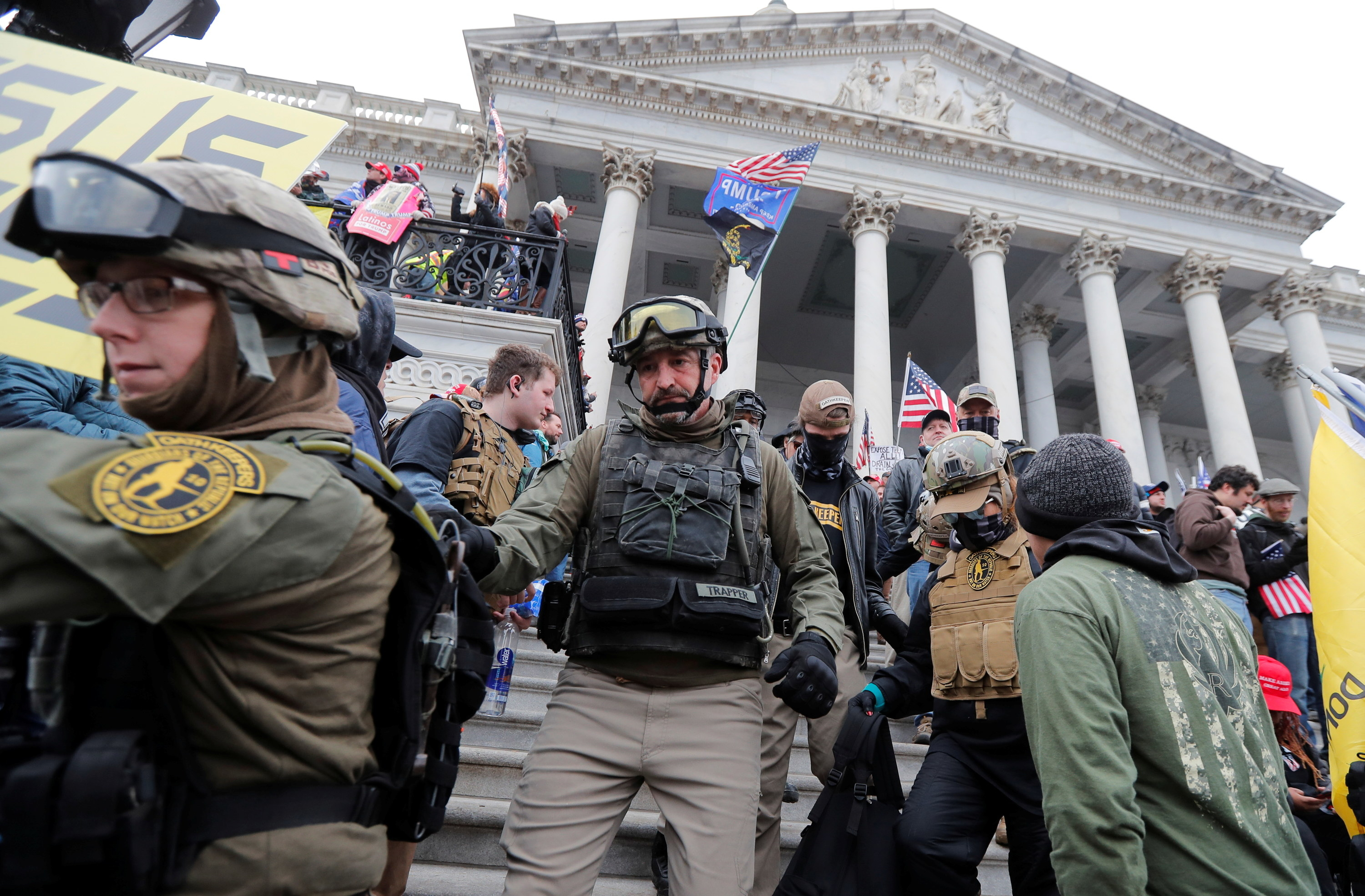 People wearing tactical gear including vests, helmets, and goggles on the Capitol steps
