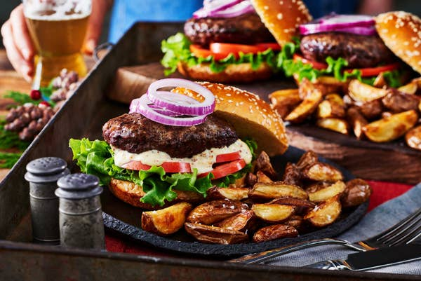 Plates of beef burgers with sides of mini wedges.