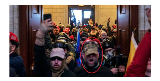 Harrelson wears a cap while marching with other rioters through a doorway in the Capitol