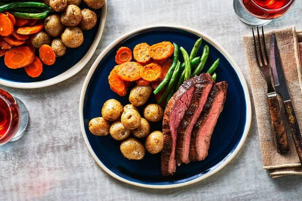 A plate with carved flank steak, green beans, roasted little potatoes, and sliced carrots.