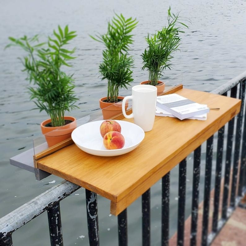 Wooden bar attached to a balcony with a plate of fruit, a mug, and some books on it
