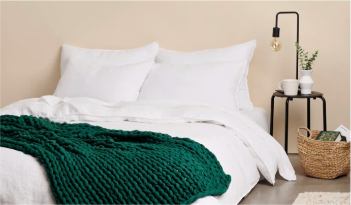 the deep green colored weighted blanket on a bed in a bedroom