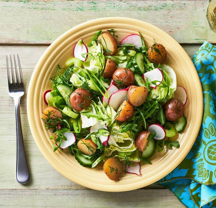 A bowl of mixed green salad with chopped radishes and little potatoes, garnished with dill.