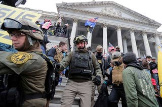 People in camo wearing tactical gear including vests, helmets, and goggles on the Capitol steps