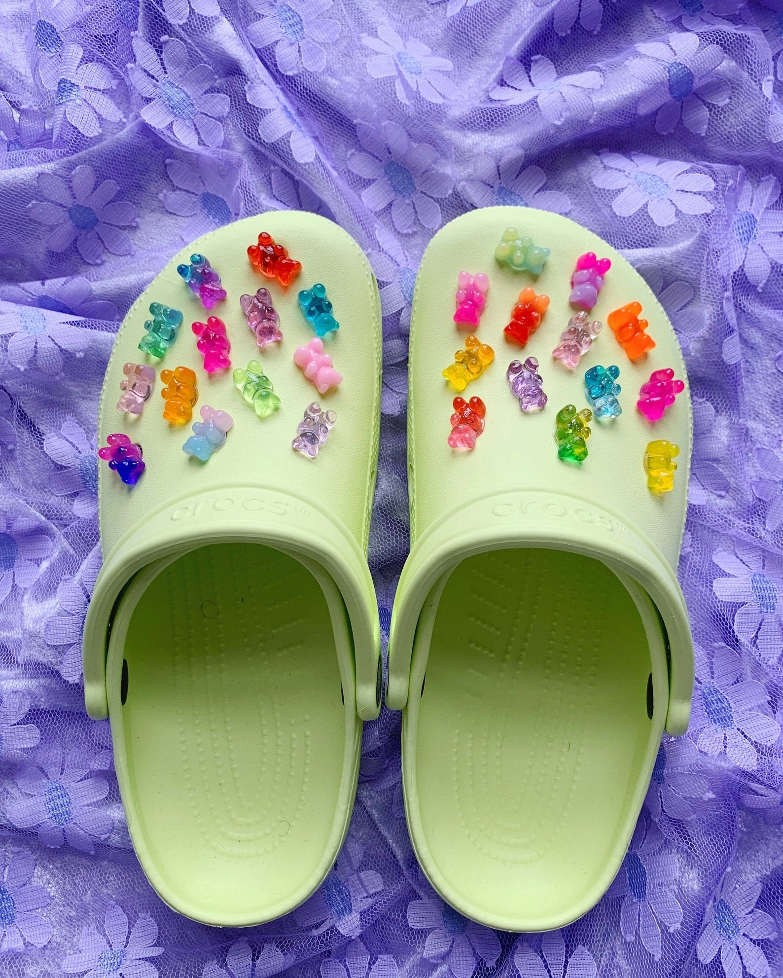 a pair of green crocs covered in gummy bear charms