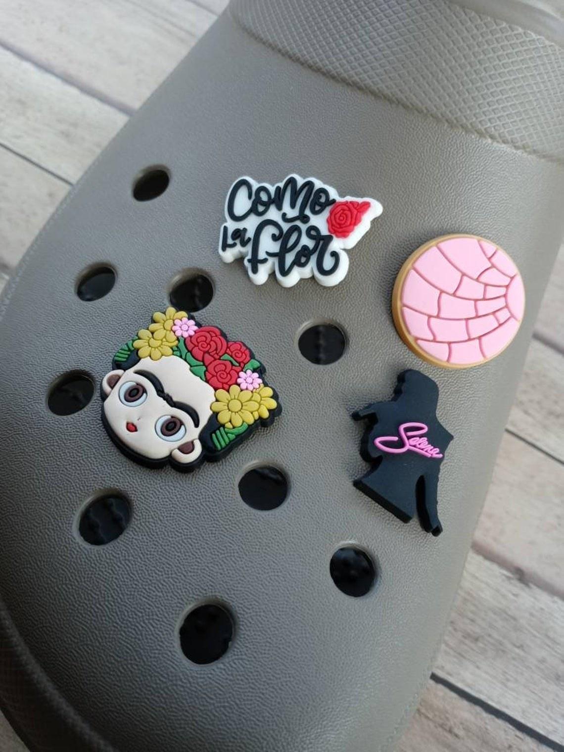 "A Croc decorated with a Frida, Selena, Concha, and ""Como la Flor"" charms"