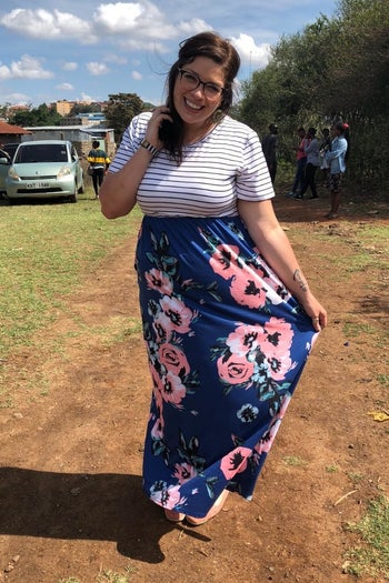 reviewer wearing the dress with a striped top and floral bottom