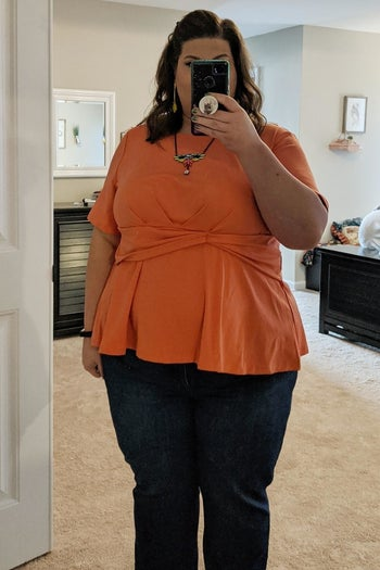 reviewer wearing the peplum top in orange with jeans