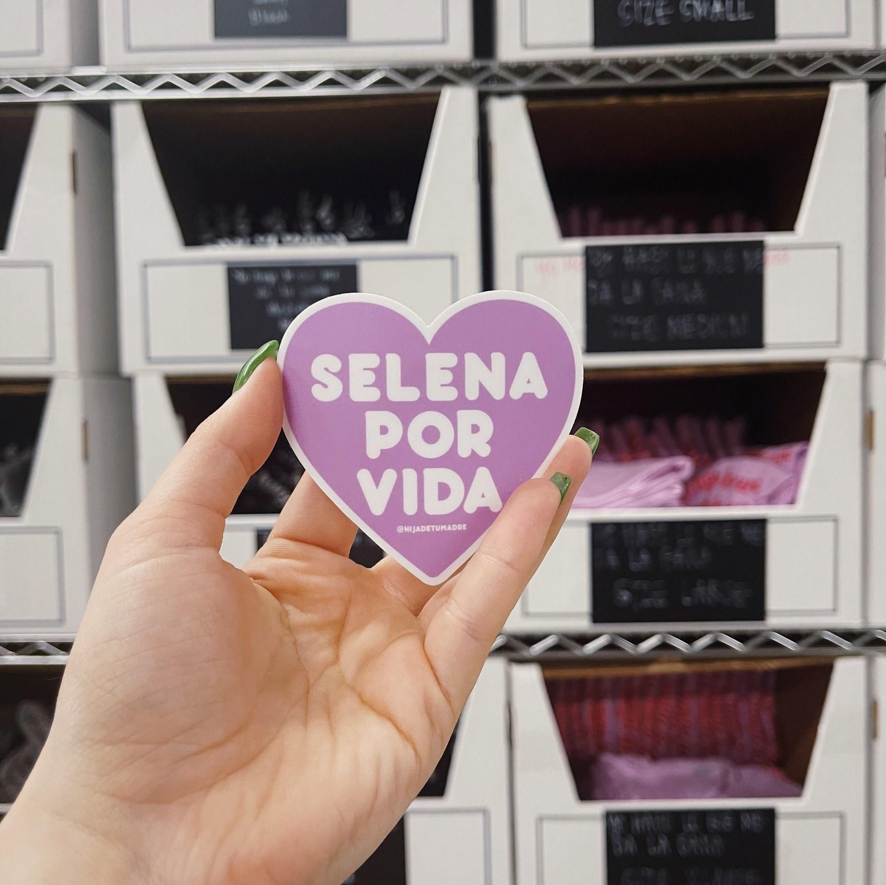 "A hand holding the matte sticker which reads, ""Selena por vida"""