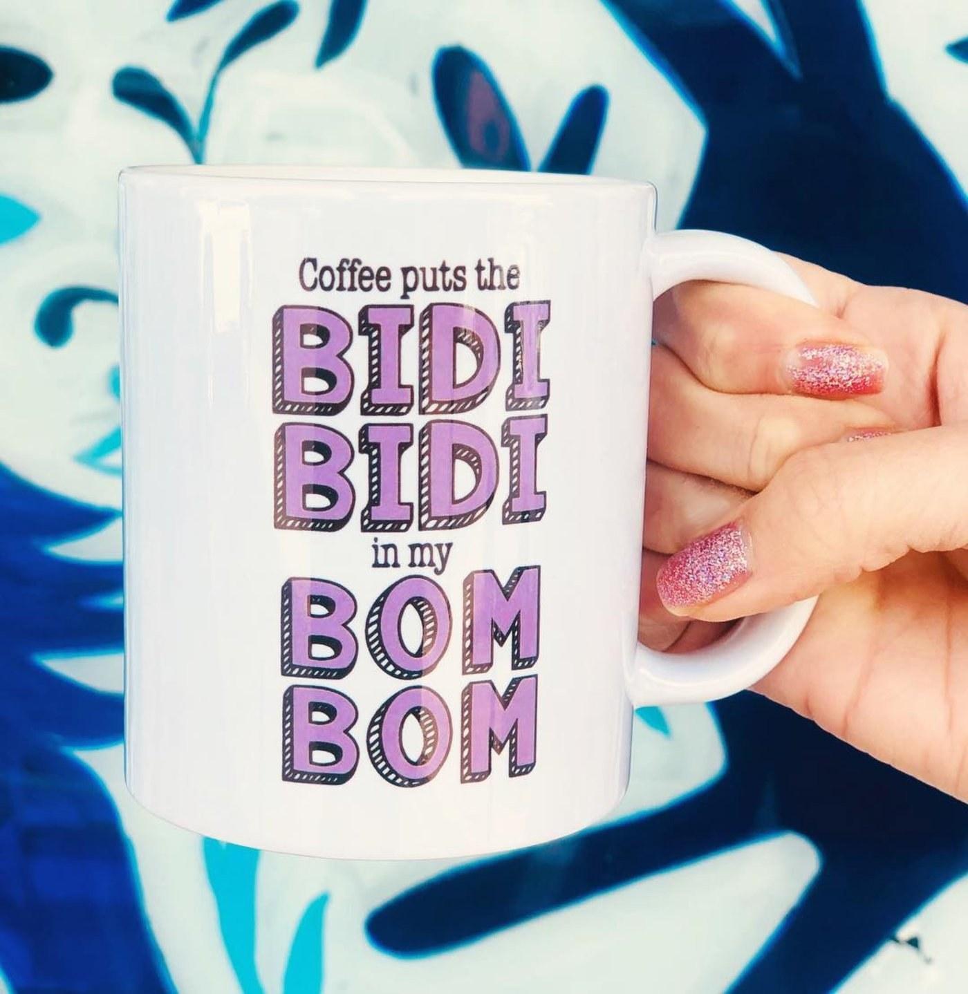 "A person holding the coffee mug that reads, ""Coffee puts the Bidi Bidi in my Bom Bom!"""