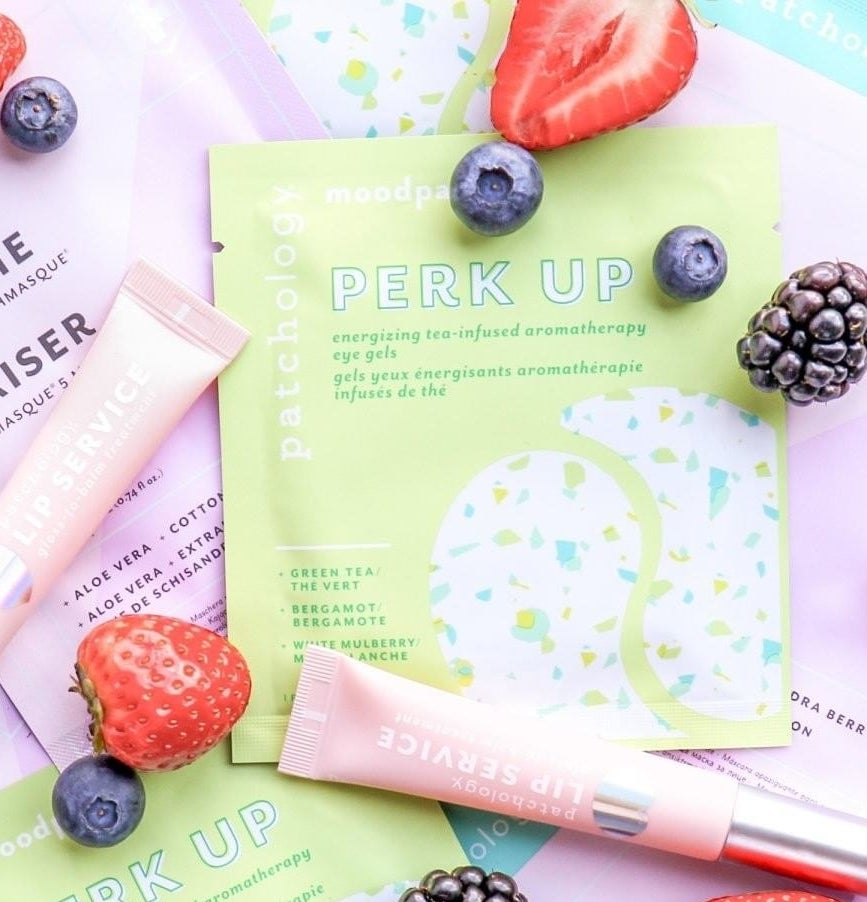 A flatlay of the eye patches next to fresh fruit and lip gloss