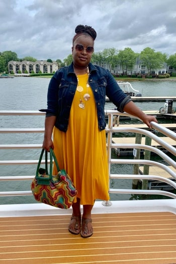 reviewer wearing the dress in yellow with a denim jacket