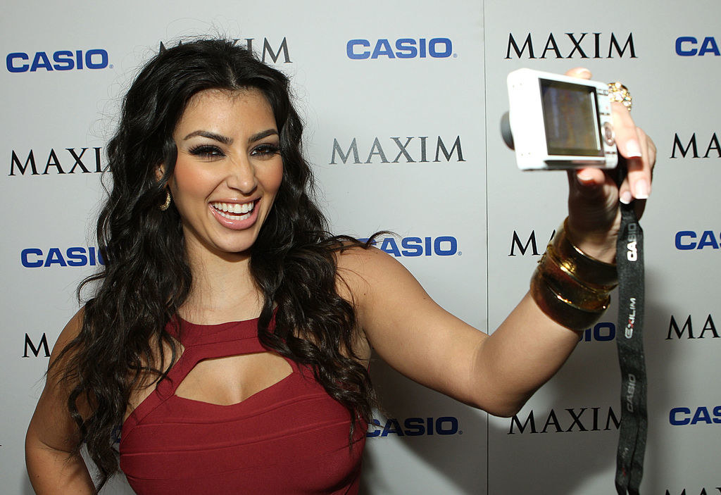 Kim Kardashian at the Maxim Style Awards taking a selfie with a digital camera