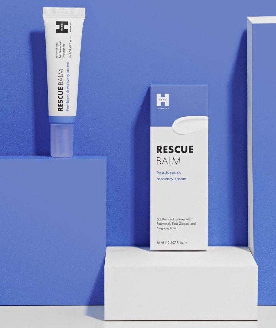 A box and tube of facial blemish recovery cream on a purple backdrop