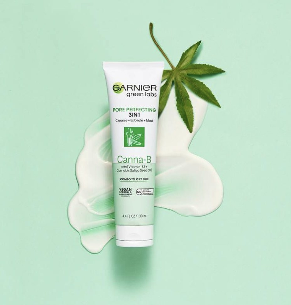 A tube of three in one cleanser on a green backdrop and cream swatch and leaf