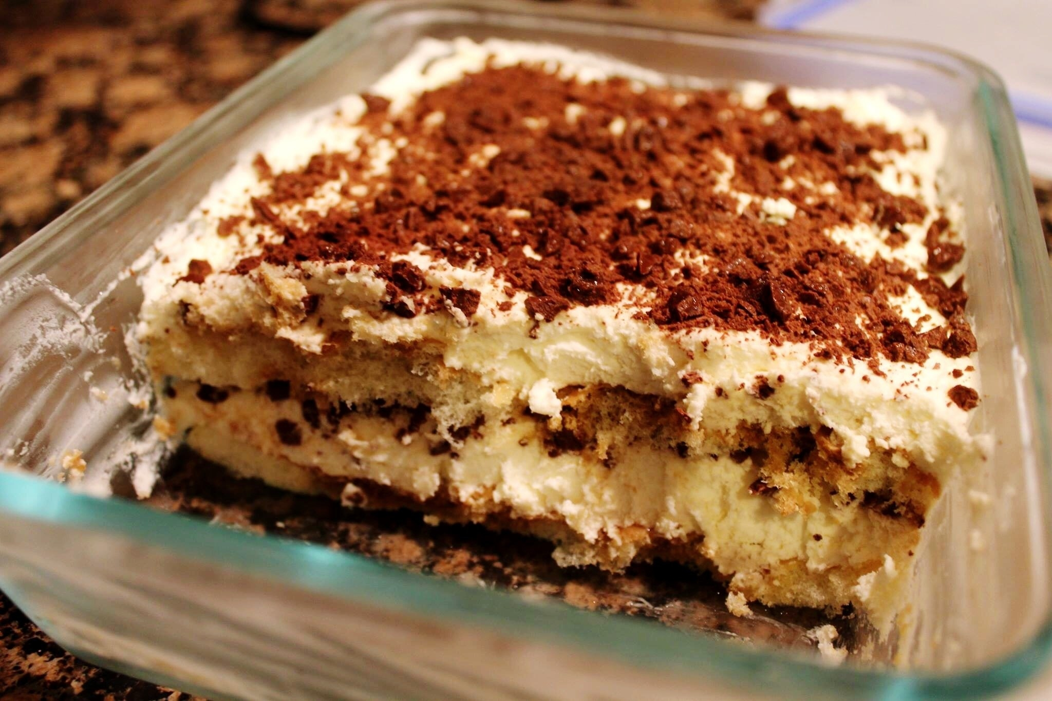 A glass container holds creamy, layered tiramisu with about 1/3 of the dessert gone