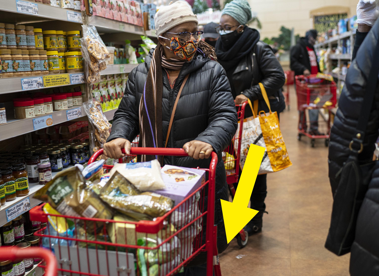 A woman pushing a shopping cart