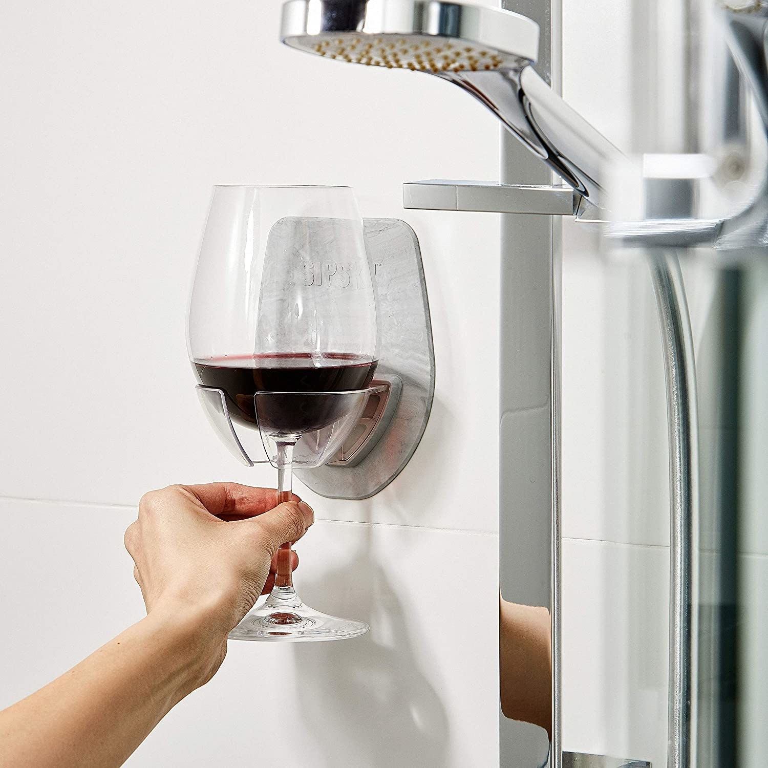 A person placing a glass of wine in the holder
