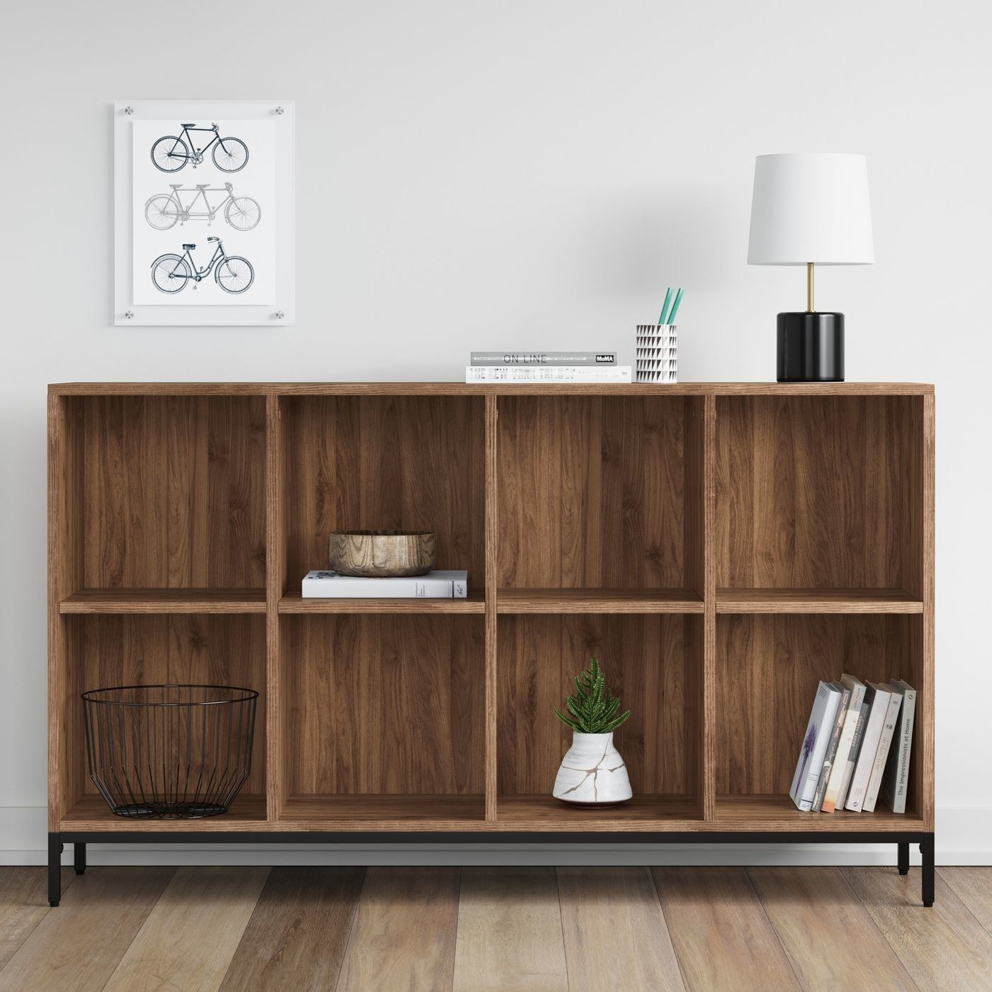 wood 8-cube bookcase with home decor on the shelves and a lamp on top