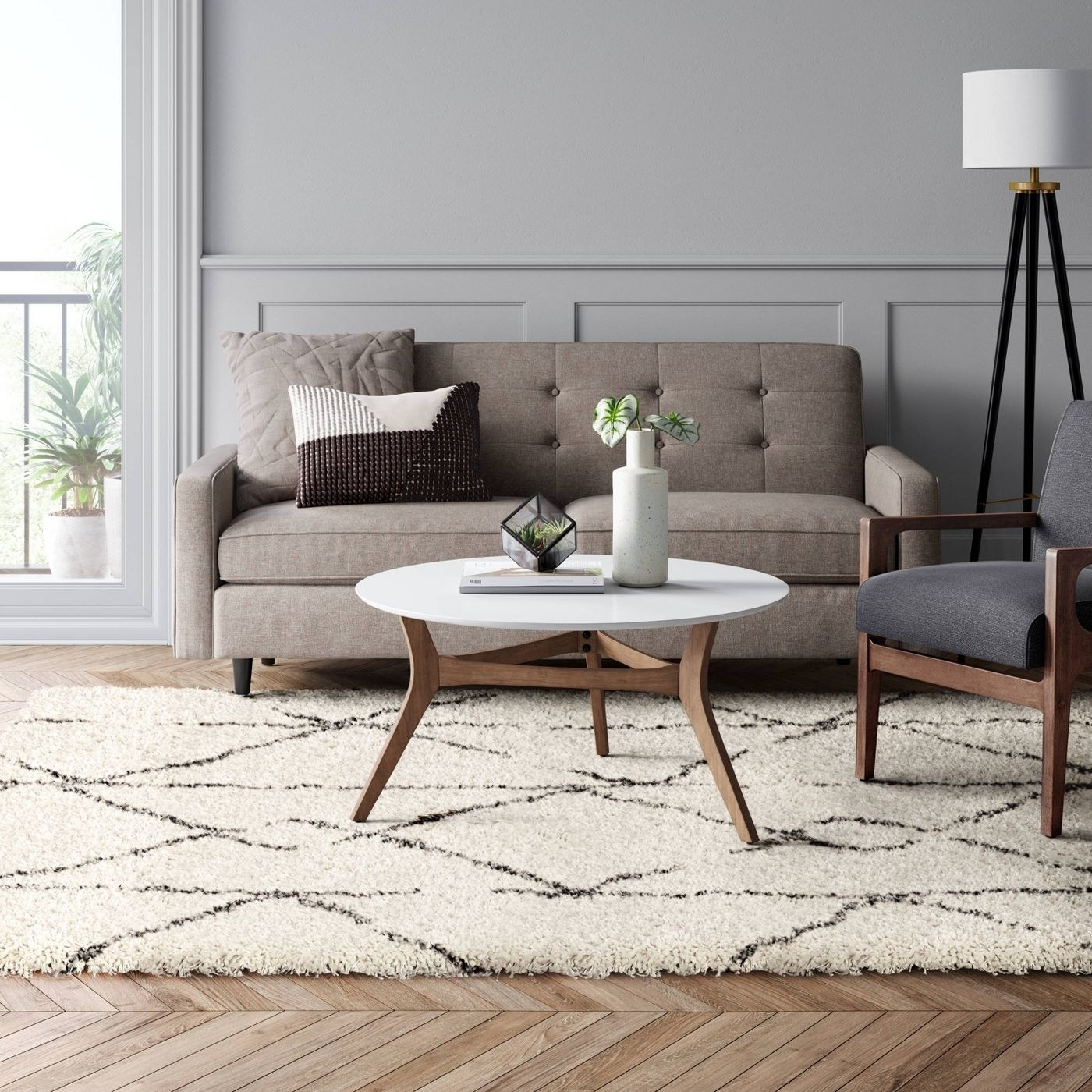 cream and grey geometric woven rug in a living room under a coffee table, couch, and chair
