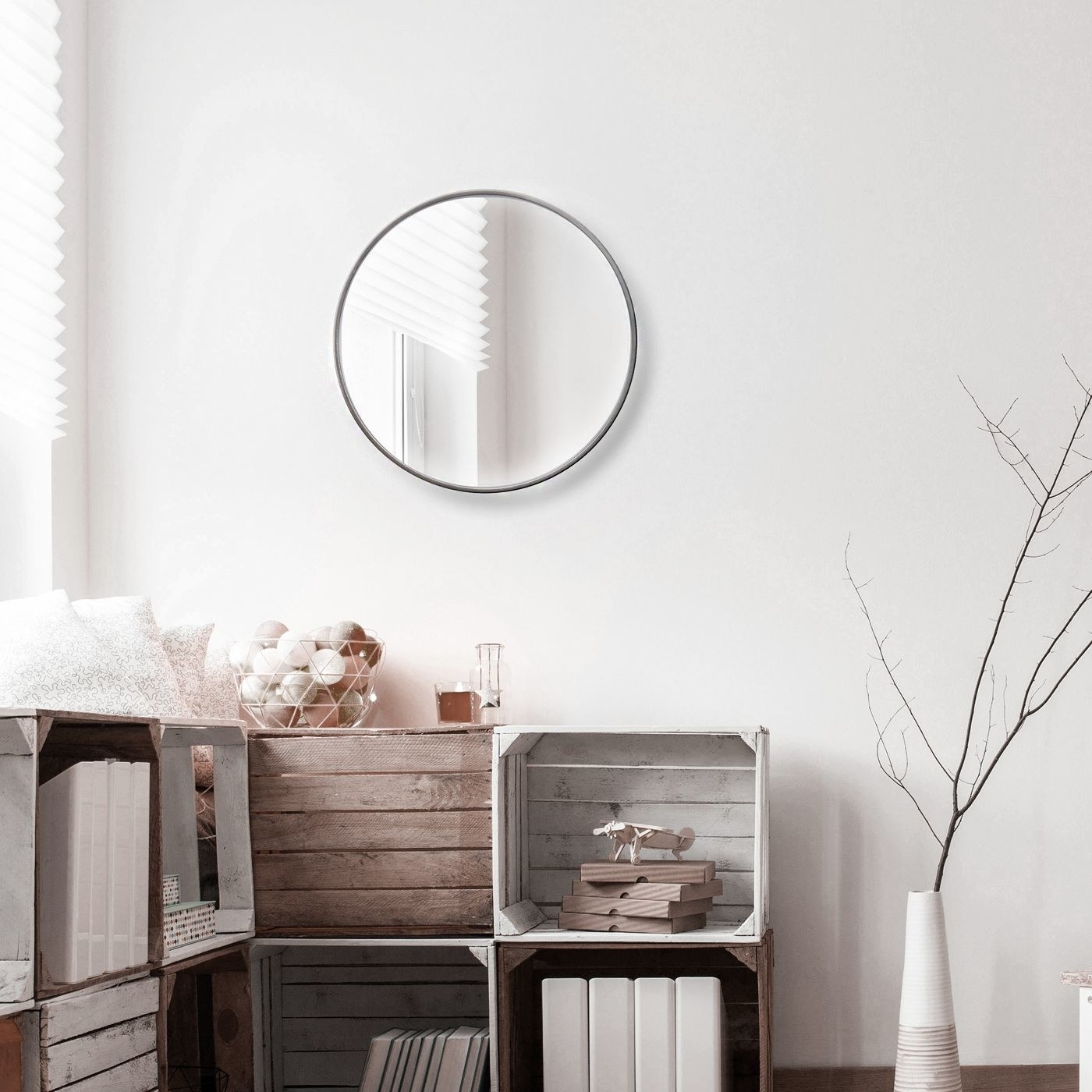 round mirror with silver border on a wall above rustic crates