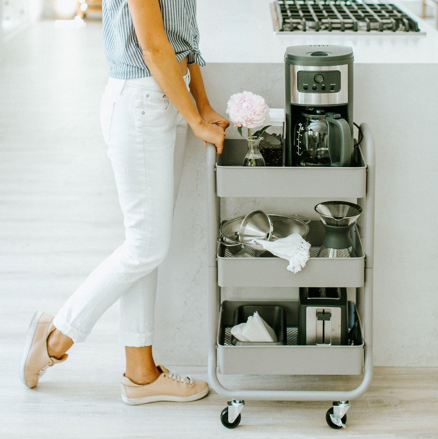 model next to a grey three-tier utility cart with small kitchen appliances on it
