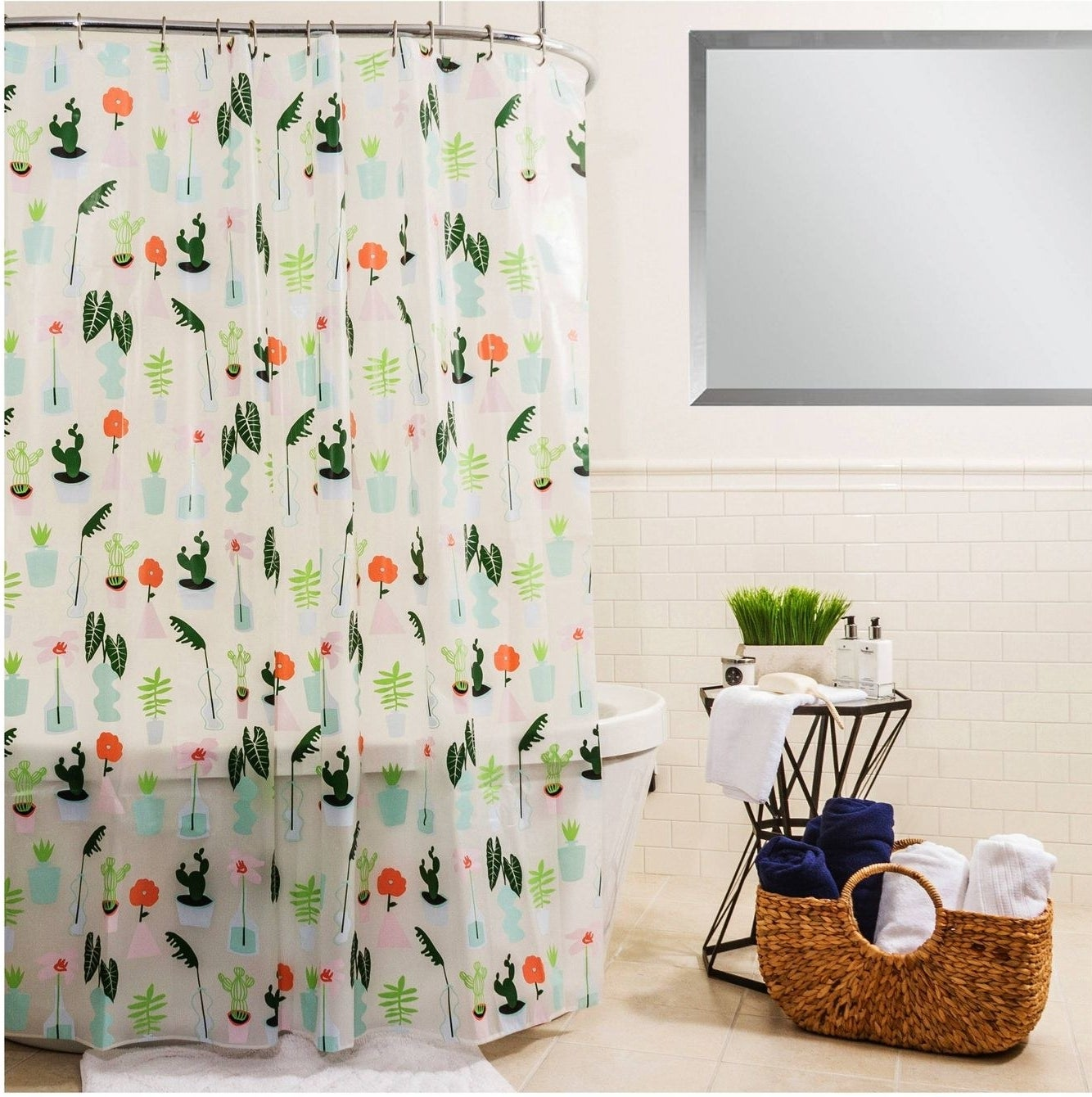 plastic shower curtain with plants print hanging above a bathtub in a bathroom