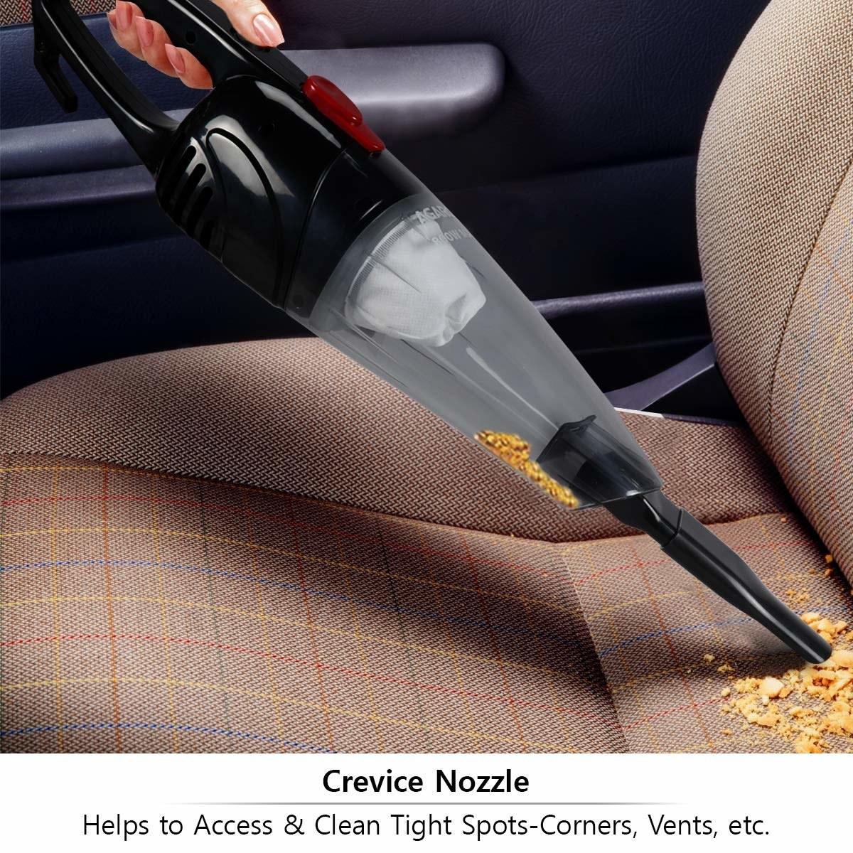 Handheld vacuum cleaner being used to clean crumbs
