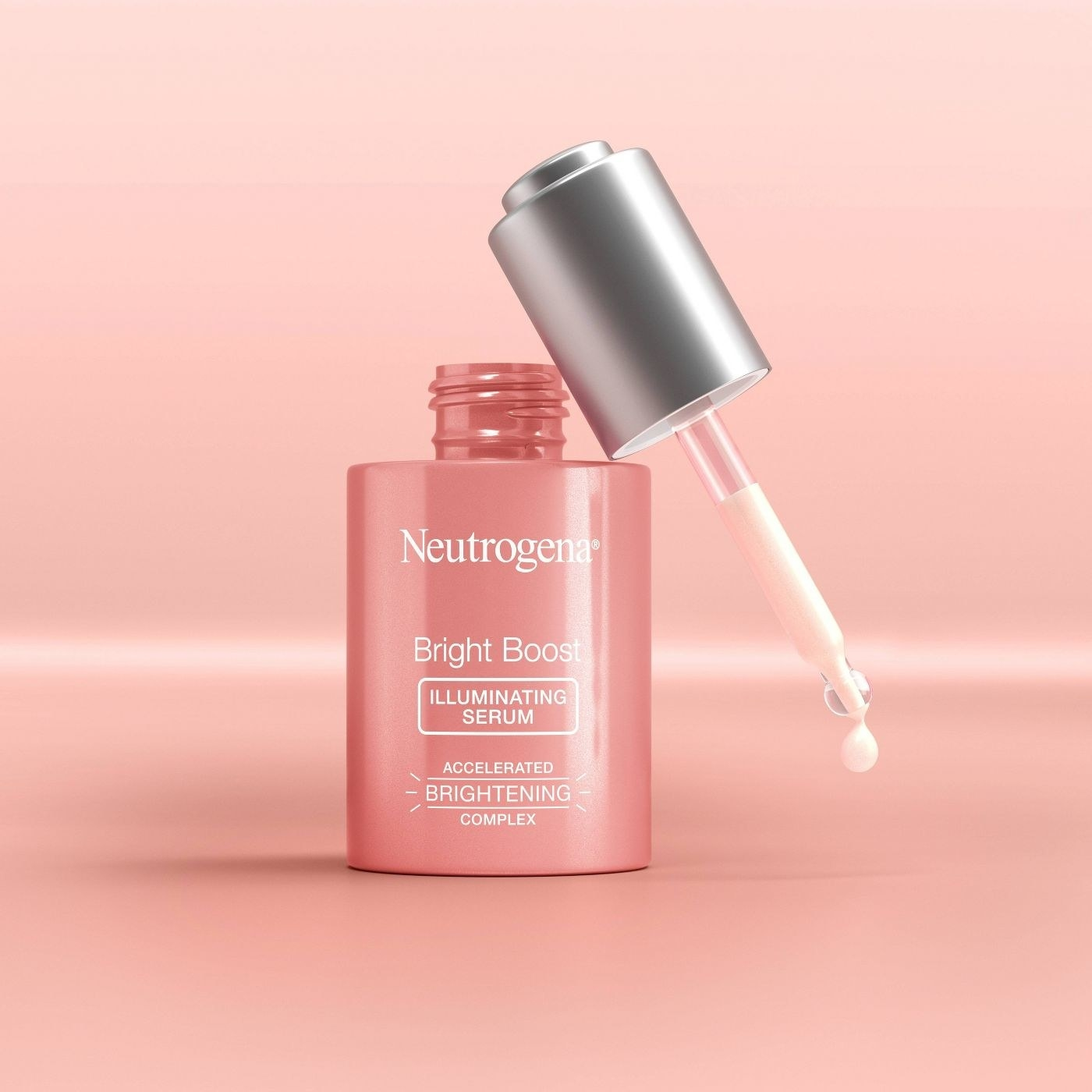 A pink dropper bottle of an illuminating serum on a pink backrop