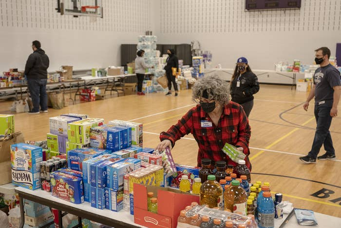 Folding tables in a school gymnasium are covered with boxes of fruit juice, Gatorade, and other food supplies