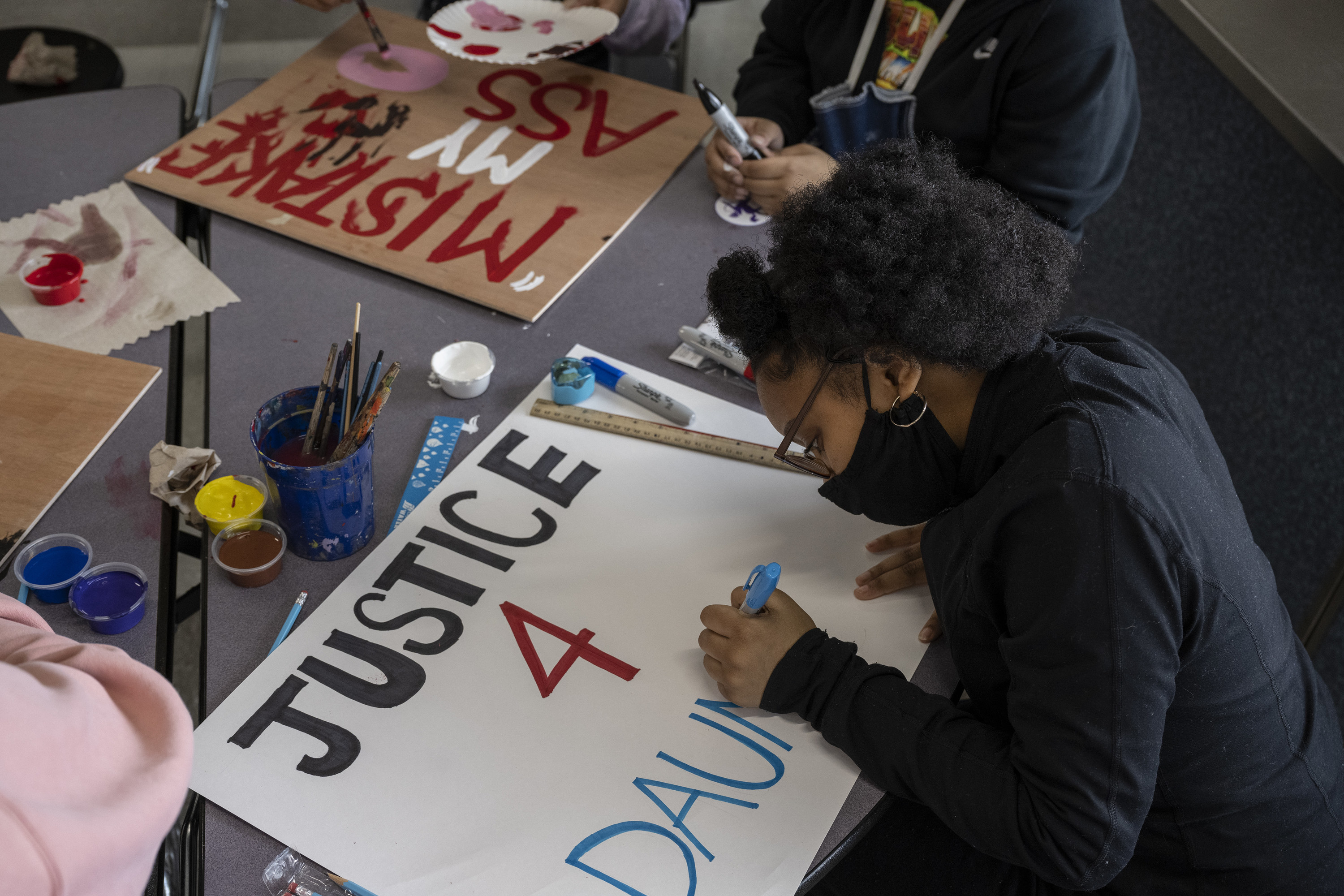 """A Black student wearing a face mask sits at a table with art supplies and fills in a protest sign that reads """"Justice for Daunte"""""""