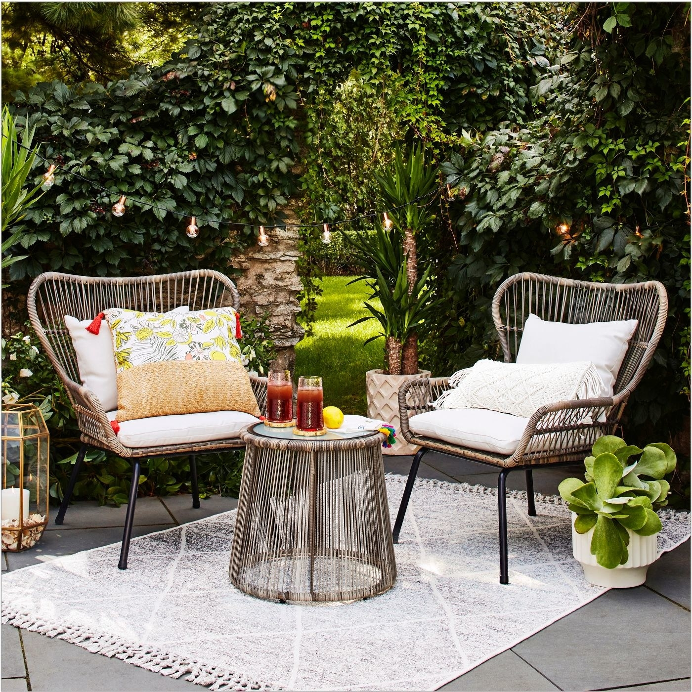 three-piece wicker patio set including two chairs with white cushions and a a round coffee table