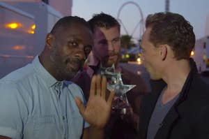 Idris waving while Chris Hemsworth and Tom Hiddleston fight behind him