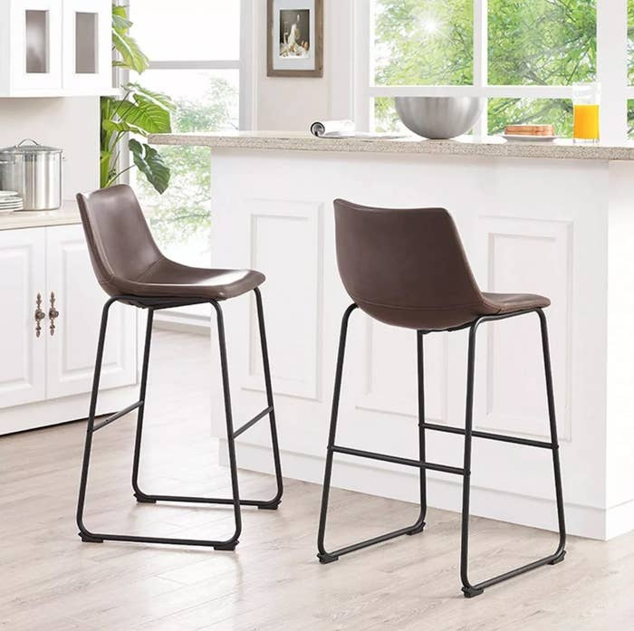 The set of two faux leather bar stools in brown with black metal legs