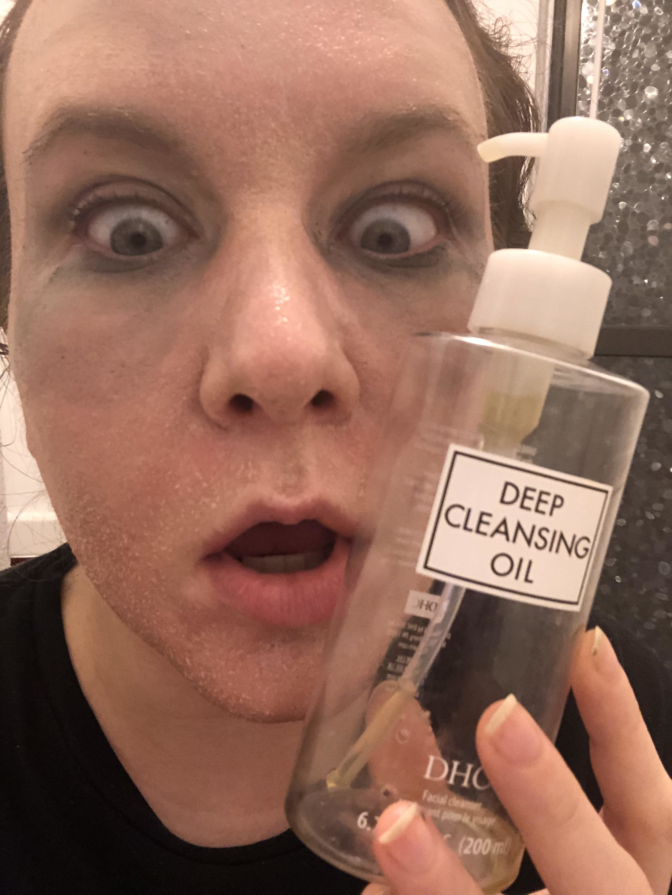 writer with foundation and mascara dissolving on face holding a bottle of the cleanser