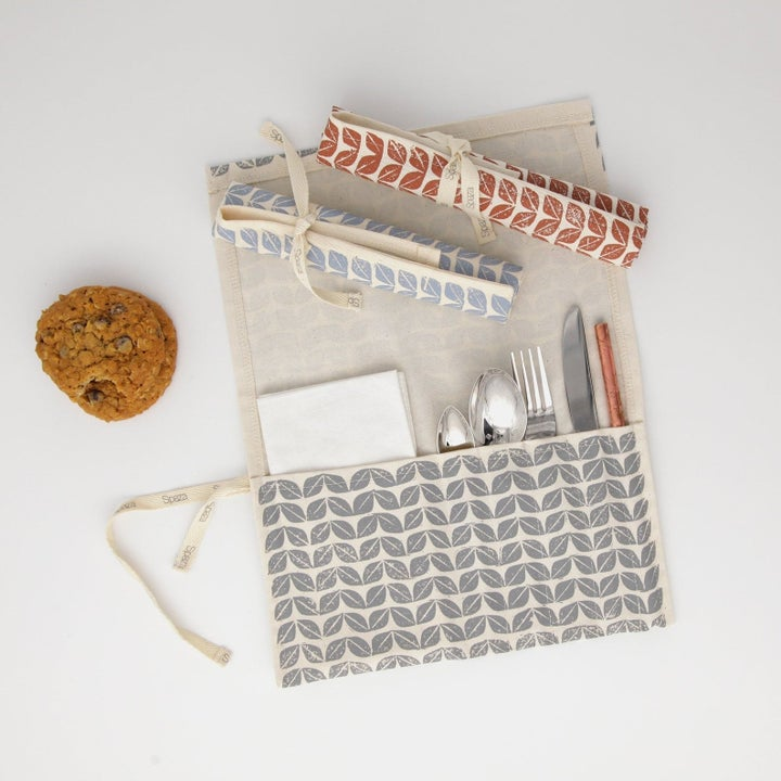 The pouch open to show slots for utensils and napkins