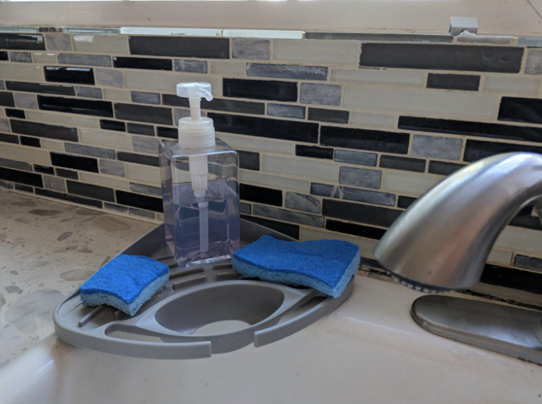 silicone corner sink organizer with a bottle of hand soap and two sponges on it