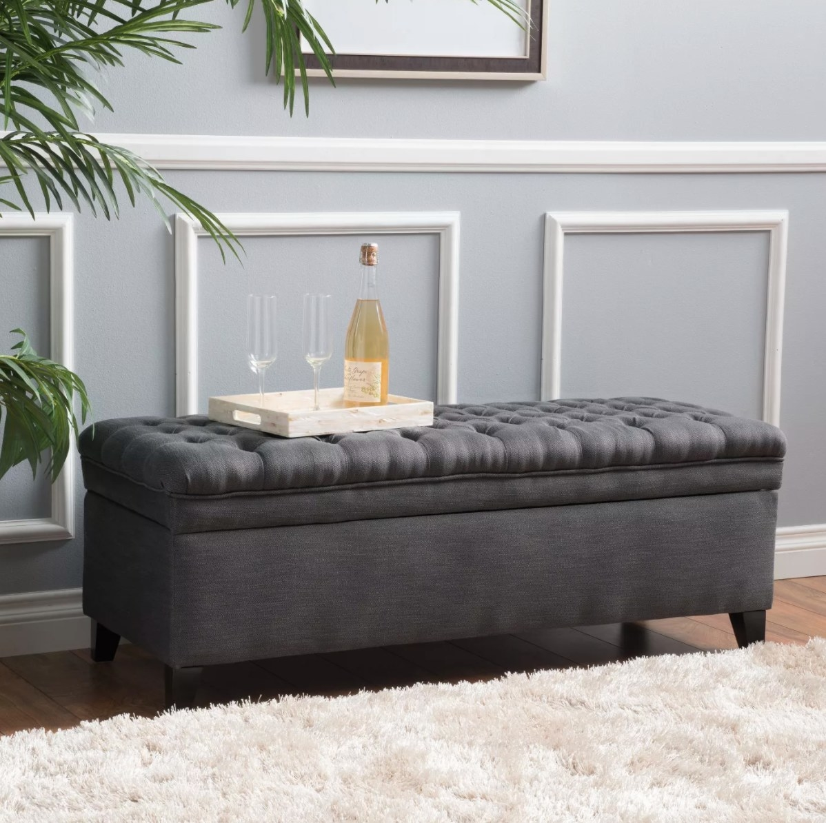 The storage ottoman in gray with a tray with flutes and champagne on top