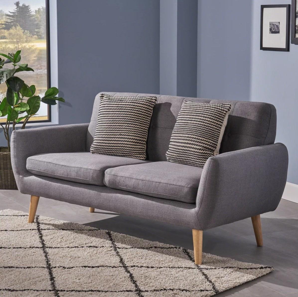 The midcentury modern sofa in dark gray with light wood legs