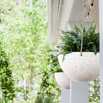 white speckled planters hanging from roof