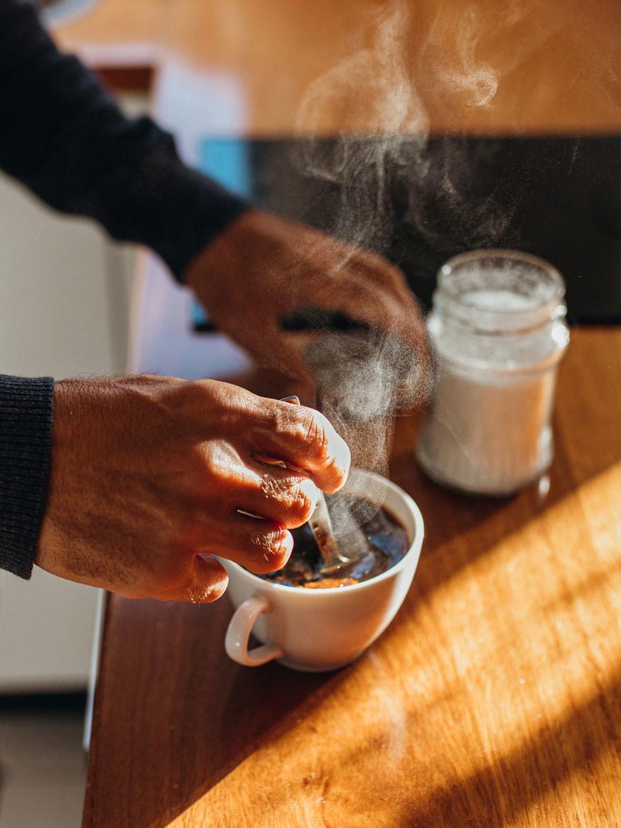 Stirring milk and sugar into coffee.