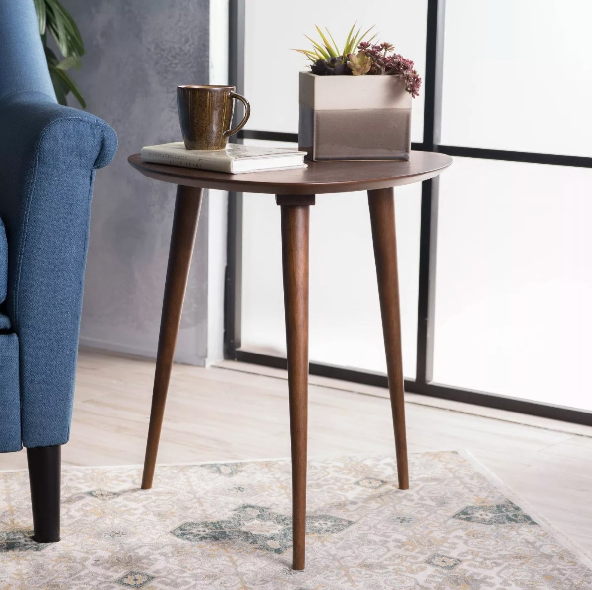 The wood end table holding a book, cup of coffee, and planter