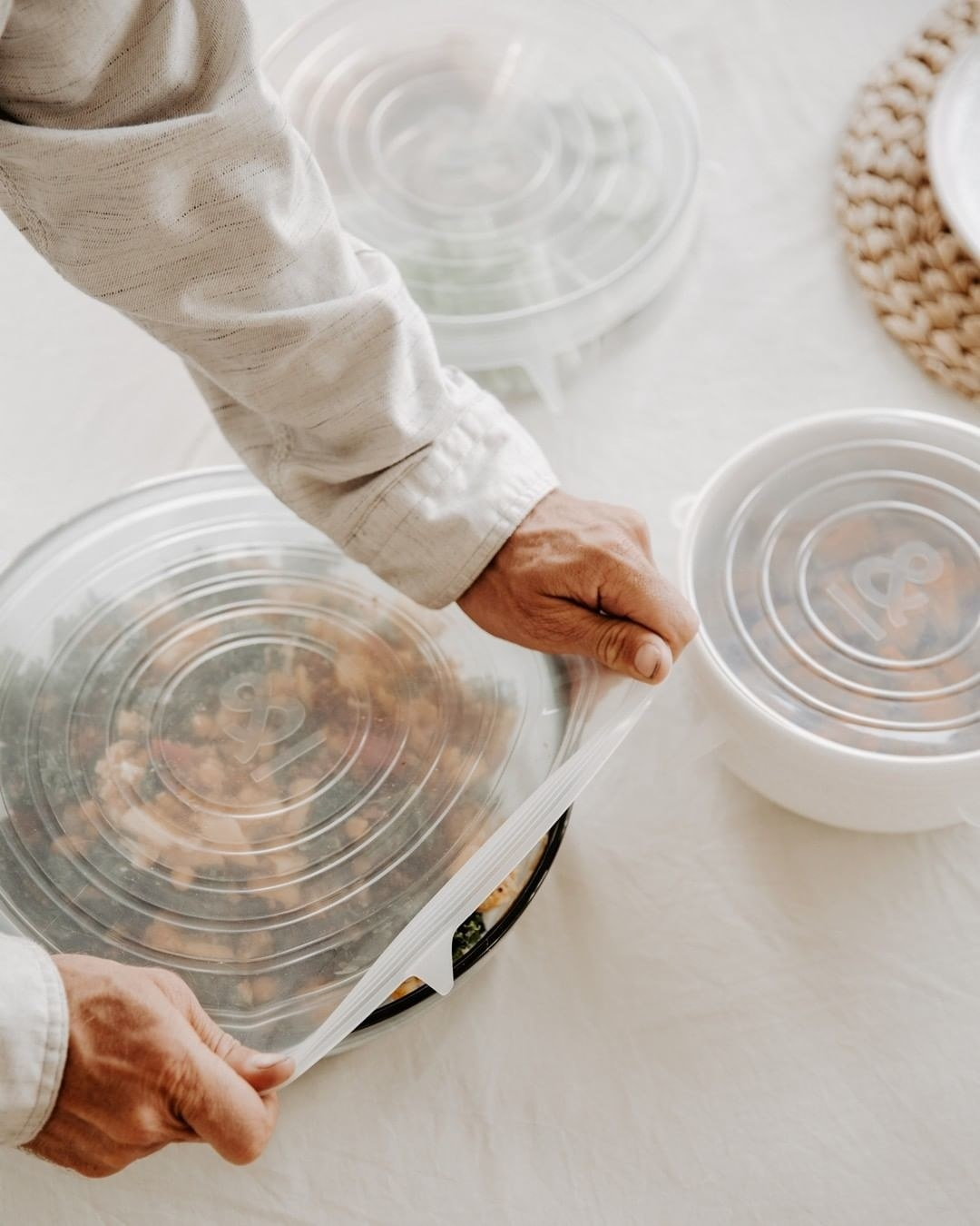 Someone stretching one of the silicone lids over a salad bowl
