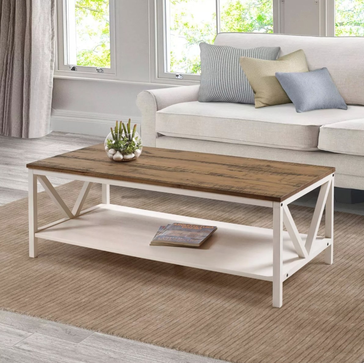 The wood farmhouse coffee table in two-toned white and barn house with a plant on top and with magazines underneath