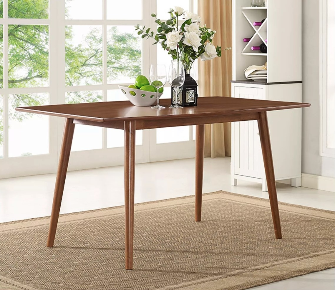 The midcentury dining table with limes, wine glasses, and a vase of flowers on top